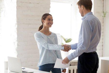 Photo pour Patron d'âge moyen confiant serrant la main d'une jeune stagiaire mixte heureuse, tenant une enveloppe avec une récompense en argent, félicitant avec de bons résultats de travail, encourageant son collègue . - image libre de droit