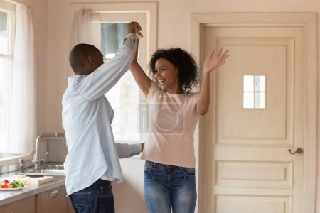 Photo for Excited african american young man dancing with happy mixed race wife, twisting, having fun together. Joyful smiling family couple moving, celebrating anniversary, enjoying weekend leisure time. - Royalty Free Image