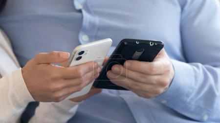 Photo pour Crop close up of man and woman hold modern smartphones browsing wireless internet on gadgets, couple use cellphones, partager le contenu des médias sociaux sur les appareils électroniques, concept de nouvelle technologie - image libre de droit
