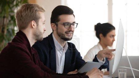 Foto de Dos colegas masculinos examinan el monitor de la computadora y discuten los resultados de los proyectos en una oficina moderna. Empleados jóvenes motivados que trabajan juntos en la investigación de mercado en el lugar de trabajo, concepto de colaboración.. - Imagen libre de derechos