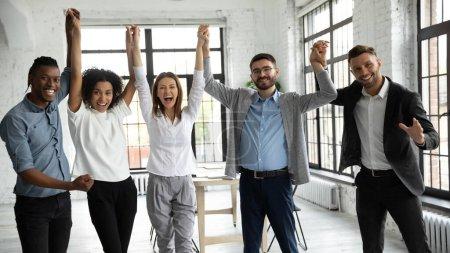 Photo pour Divers gens d'affaires excités célébrant le succès, tenant la main levée, regardant la caméra, souriant joyeux employés équipe réjouissant réalisation, rire et crier de joie dans la salle de bureau - image libre de droit