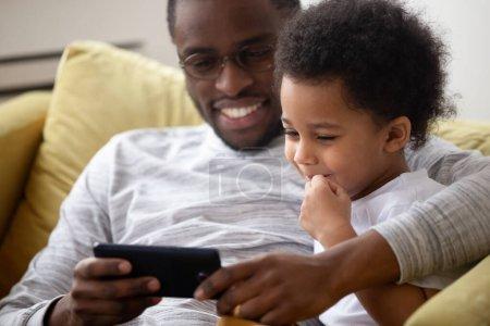 Photo pour Gros plan Le père attentionné américain passe du temps avec la petite famille de son fils assis sur le canapé en utilisant un smartphone en regardant des dessins animés s'amuser profiter de l'application en ligne pour les enfants. Contrôle parental week-ends paresseux concept d'activité - image libre de droit