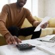 African ethnicity man sitting on couch calculates ...