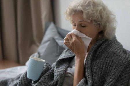 Photo pour Malade femme mûre s'asseoir se détendre dans le lit sous la couverture chaude coup de nez en cours d'exécution en utilisant des tissus, boire du thé chaud de la grippe, malade femme âgée souffrent de grippe ou grippe à la maison, concept de soins de santé aux personnes âgées - image libre de droit