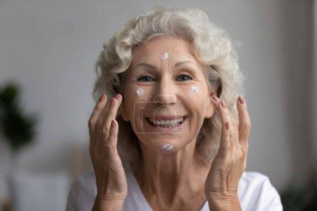 Portret szczęśliwej dojrzałej kobiety używającej kremu przeciw wiekowi