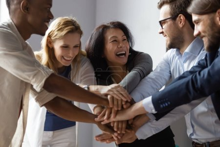 Photo for Close up image overjoyed 5 multi ethnic business people stack touch arms palms together celebrating promotion reward, succeed common aim. Give high five symbol of unity, team building activity concept - Royalty Free Image