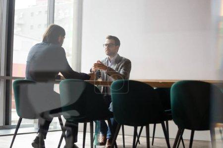 Photo pour Processus de négociation derrière le concept de porte murale, gestionnaire des ressources humaines interviewant le candidat de la position de l'entreprise, deux hommes d'affaires réunion d'affaires, courtier d'assurance fait affaire avec le client de l'entreprise - image libre de droit