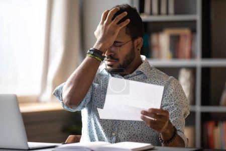 Foto de Empresario africano estresado sentado en el escritorio sostiene carta de papel leyendo malas noticias negativas horribles fue despedido del trabajo. Notificación de despido, problemas financieros notificación de la deuda del banco, concepto de factura no pagada - Imagen libre de derechos