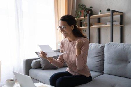 Photo pour Femme excitée portant des lunettes lettre de lecture avec de bonnes nouvelles, célébrant le succès, montrant oui geste, souriant fille réjouie de succès, résultats d'examen positifs, promotion de l'emploi, remboursement de l'argent - image libre de droit