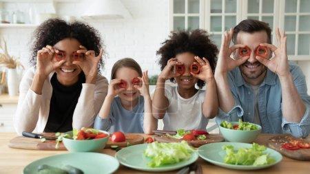 Foto de En pareja de cocina y multi hijas raciales preparan ensalada de verduras que se divierten hacen caras divertidas cubren los ojos con círculos de pimentón rojo que parecen gafas, binoculares forma, cocina, concepto de alegría familiar - Imagen libre de derechos