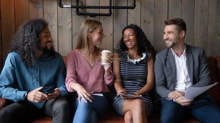 Photo pour Quatre collègues multiethniques se reposent dans le café pendant la pause déjeuner boire du café profiter de la conversation. Candidats drôles parler tout en attendant entrevue d'emploi amity express et relation amicale, maintenez les dispositifs et cv - image libre de droit