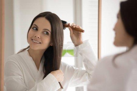 Photo pour Miroir reflet tête tourné souriant belle jeune femme peigner les cheveux avec brosse en bois après la douche, satisfait jolie fille portant peignoir blanc debout dans la salle de bain, profiter de la routine du matin - image libre de droit