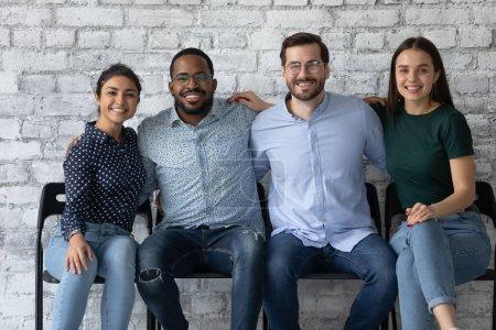 Photo pour Quatre étudiants multiethniques sympathiques employés de bureau assis ensemble sur des chaises embrassant sourire en regardant la caméra. Relations chaleureuses entre les membres de l'entreprise, amitié et amitié, concept d'égalité raciale - image libre de droit