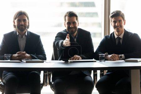 Photo pour Souriant jeune homme amical hr managers en costumes assis à la table, regardant la caméra, tendre la main pour accueillir prometteur demandeur d'emploi, faire une offre de recrutement ou accueillir les nouveaux arrivants, processus d'embauche. - image libre de droit