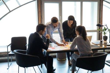 Photo pour Des gens d'affaires concentrés et diversifiés se réunissent au bureau pour travailler ensemble à l'analyse de la paperasserie d'entreprise, des collègues de travail discutent de documents financiers lors d'une réunion, concept de coopération - image libre de droit