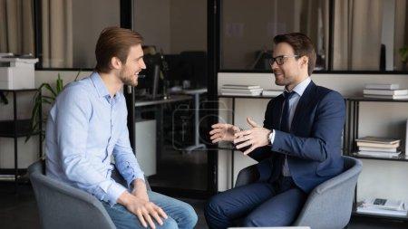Photo pour Heureux jeunes hommes d'affaires caucasiens assis dans le bureau parler blague et rire au bureau pendant la pause de travail, souriant collègues masculins ou les employés ont plaisir à bavarder lors d'une réunion occasionnelle ou briefing sur le lieu de travail - image libre de droit