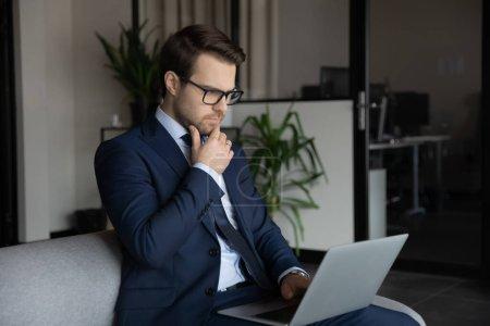 Photo pour Homme d'affaires caucasien sérieux pensif dans des lunettes et costume formel regarder l'écran d'ordinateur portable penser à la solution de problème d'affaires, travail réfléchi d'employé de patron masculin sur ordinateur, réfléchir ou analyser - image libre de droit