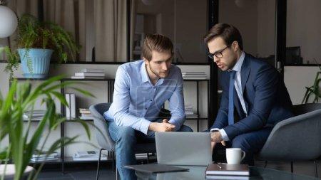 Photo pour Homme d'affaires caucasien concentré en costume formel parler remue-méninges coopérer avec un collègue masculin à la réunion au bureau, les hommes sérieux partenaires d'affaires regardent ordinateur portable discuter projet financier ensemble - image libre de droit