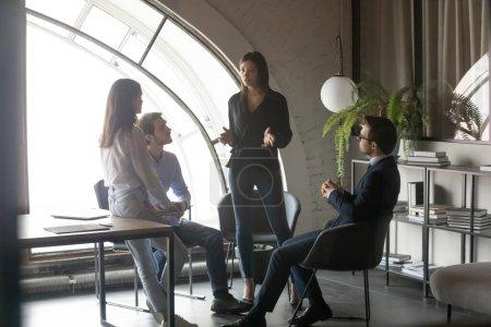 Photo pour Une jeune femme d'affaires ethnique confiante dirige une réunion avec un employé diversifié lors d'une réunion informelle au bureau, une dirigeante motivée discute de remue-méninges avec ses collègues lors d'une séance d'information, de leadership et de travail d'équipe - image libre de droit