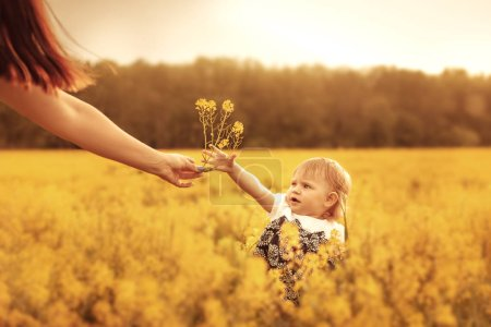 Mom gives flowers to her little daughter. Sunset o...