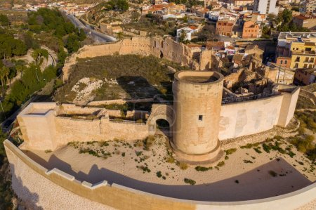 Photo for Aerial panoramic view of medieval Elda castle above the town with partially restored walls, towers and gate made of white lime stone in Spain - Royalty Free Image