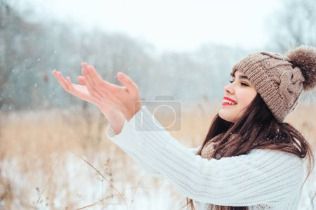 happy woman catching snowflakes on the walk in snowy winter park. Spending vacations outdoor, seasonal activities concept