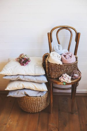 Photo for Cozy interior details, scandinavian mininalistic lifestyle. Organizing clothes in wicker backets, seasonal wardrobe and house cleaning, ideas for winter season. - Royalty Free Image