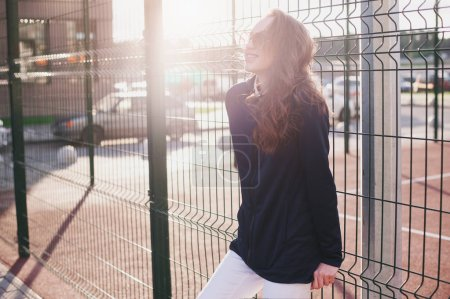 Photo pour Une belle fille en lunettes de soleil un soir d'été se tient debout et sourit près du terrain de basket - image libre de droit