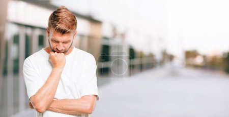 young blonde man With a confused and thoughtful look, looking sideways, thinking and wondering between different options.
