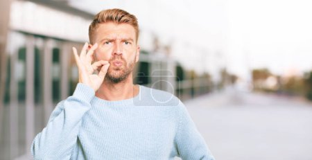 """young blonde man gesturing """"zip it"""" with hand, demanding silence or secrecy with a serious, stern look."""