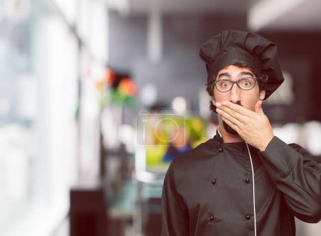 young crazy man as a chef Covering mouth with hand with a gesture of surprise, in order to remain silent and keep a secret.
