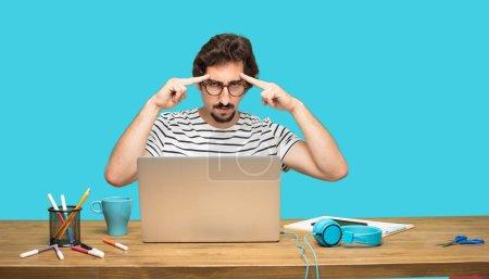 jeune designer barbu concentration dure sur une idée, avec un air sérieux, en pensée avec les deux doigts index pointant sur le front