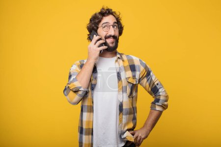 Photo pour Jeune homme fou fou fou pose avec un téléphone mobile intelligent - image libre de droit