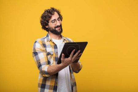 Photo pour Jeune homme fou fou dans fool pose avec écran tactile tablette intelligente - image libre de droit