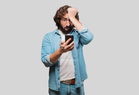 Photo pour Young fool man with a smartphone - image libre de droit
