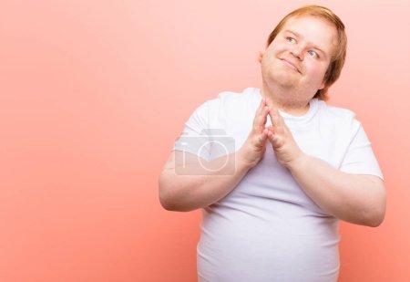 Photo pour Jeune homme de grande taille se sentant fier, espiègle et arrogant tout en complotant un plan maléfique ou en pensant à un truc contre un mur rose - image libre de droit