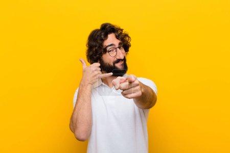 Photo pour Jeune fou souriant joyeusement et pointant vers la caméra tout en vous appelant plus tard geste, parler au téléphone contre mur jaune - image libre de droit