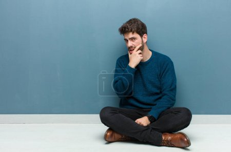 Young handsome man sitting on floor with mouth and...