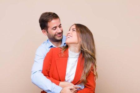 Photo pour Jeune joli couple contre beige mur plat - image libre de droit