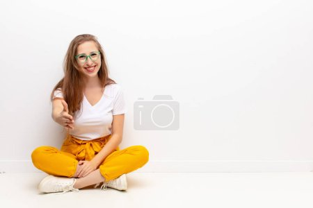 Photo for Yound blonde woman smiling, looking happy, confident and friendly, offering a handshake to close a deal, cooperating sitting on the floor - Royalty Free Image
