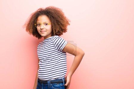 Photo pour Afro-américaine petite fille contre mur plat avec un portefeuille - image libre de droit
