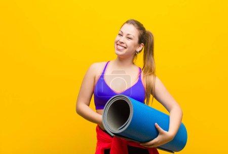 Foto de Joven rubia con una esterilla de yoga. concepto deportivo - Imagen libre de derechos