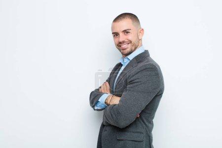 Photo pour Jeune homme d'affaires souriant à la caméra avec les bras croisés et une expression heureuse, confiante, satisfaite, vue latérale contre un mur plat - image libre de droit