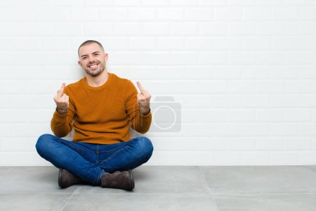 Photo for Young handsome man feeling provocative, aggressive and obscene, flipping the middle finger, with a rebellious attitude sitting on the floor - Royalty Free Image