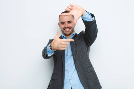 Photo for Young businessman feeling happy, friendly and positive, smiling and making a portrait or photo frame with hands against flat wall - Royalty Free Image