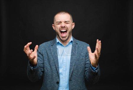 Foto de Joven empresario furiosamente gritando, sintiéndose estresado y molesto con las manos arriba en el aire diciendo por qué me contra la pared plana - Imagen libre de derechos