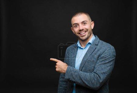 Photo pour Jeune homme d'affaires regardant excité et surpris pointant vers le côté et vers le haut pour copier l'espace contre un mur plat - image libre de droit