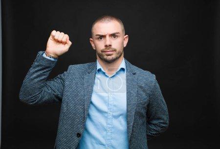 Photo pour Jeune homme d'affaires se sentant sérieux, fort et rebelle, levant le poing, protestant ou luttant pour la révolution contre un mur plat - image libre de droit