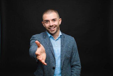 Photo pour Jeune homme d'affaires souriant, regardant heureux, confiant et amical, offrant une poignée de main pour conclure un accord, coopérant contre un mur plat - image libre de droit
