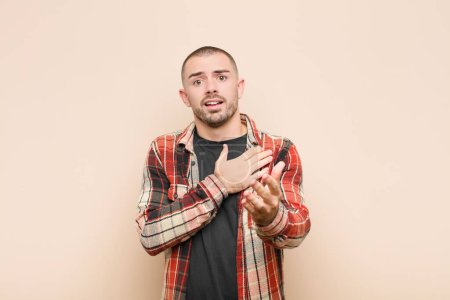 Photo for Young handsome man feeling happy and in love, smiling with one hand next to heart and the other stretched up front against flat wall - Royalty Free Image